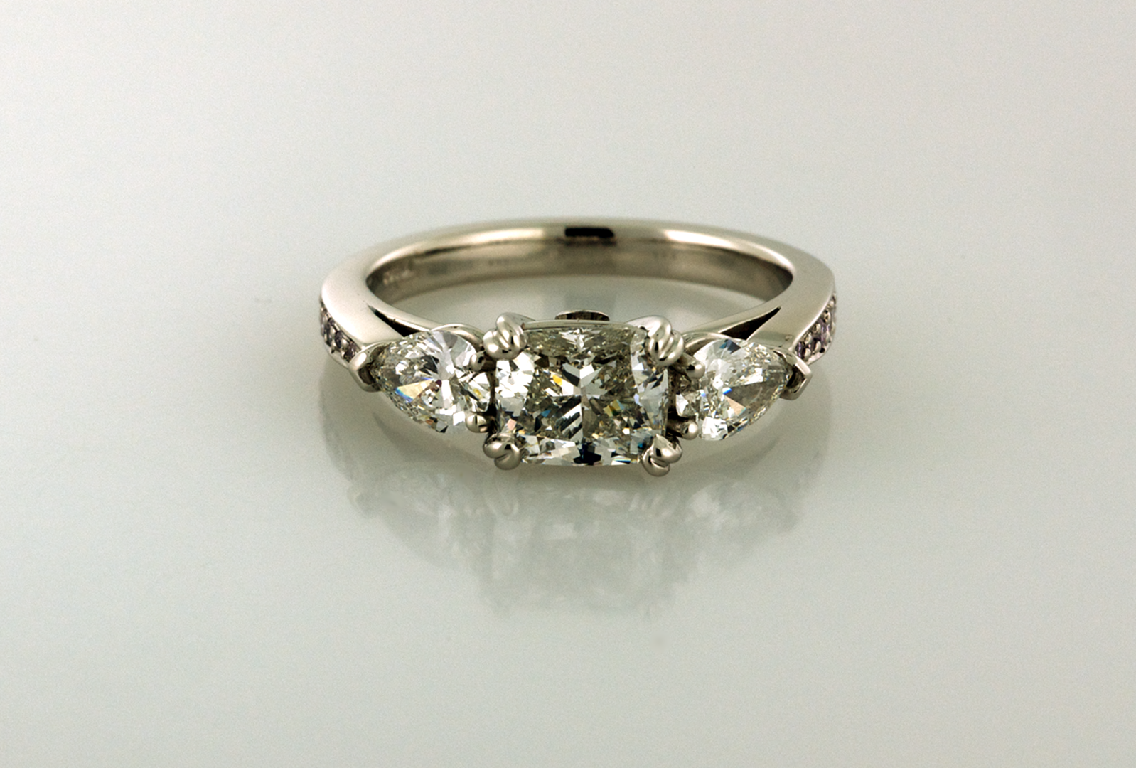 Three stone diamond platinum ring with cushion cut and pear cut side diamonds