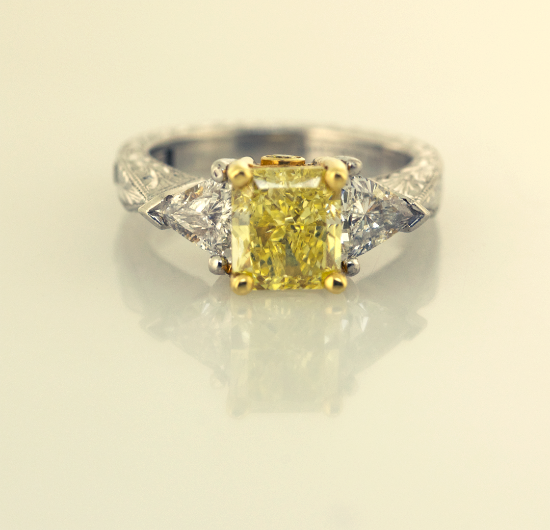 Fancy intense  yellow radiant cut diamond set with 2 trillians in Plat & 18KT