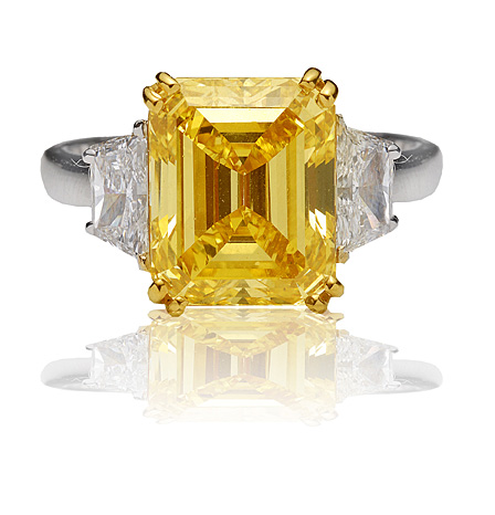 Natural yellow color diamond, emerald cut set in platinum and white baguettes