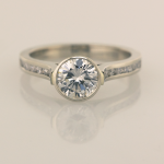 Bezel set center, cathedral ring with .15ct channel set diamonds