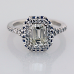 Emerald cut diamond with sapphire and diamond surround engagement ring