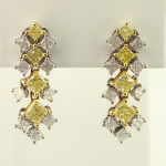 White and yellow diamond articulating earrings.