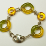 Sterling Silver & glass bracelet by Nora, green & gold