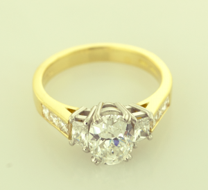 Three Stone Ring in Platinum and 18KT yellow set with oval center diamonds and trapezoid side diamonds.