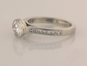 Bezel set center, cathedral ring with .15ct channel set diamonds Side view