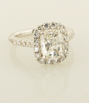 Cushion cut center diamond with diamond surround solitaire side