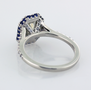 Emerald cut diamond with sapphire and diamond surround engagement ring Back view