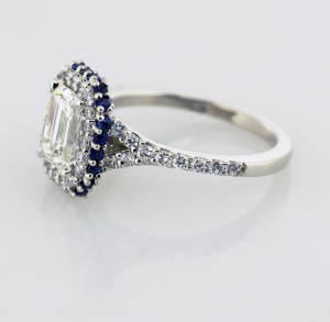 Emerald cut diamond with sapphire and diamond surround engagement ring Side view