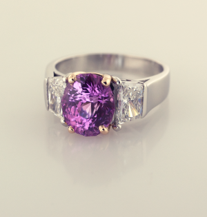 Pink sapphire 4.50ct. and1.25ct. trapezoid diamondsthree stone platinum and 18KT rose gold ring.