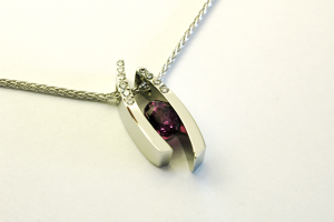 Purple sapphire (3.50ct.) set in 14KT white gold pendant with diamond accents