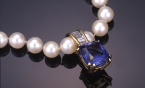 Tanzanite 4.50ct and 1.20ct.diamond baguette pendant set in 18KT gold on strand of pearls