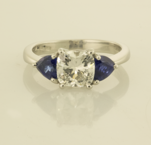 Platinum cushion cut diamond and trillion sapphire ring.