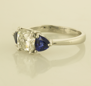 Platinum cushion cut diamond and trillion sapphire ring side view
