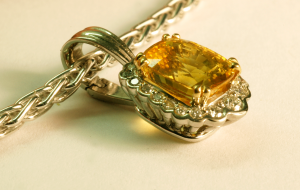 Yellow Sapphire with surround diamonds in 18KT white gold
